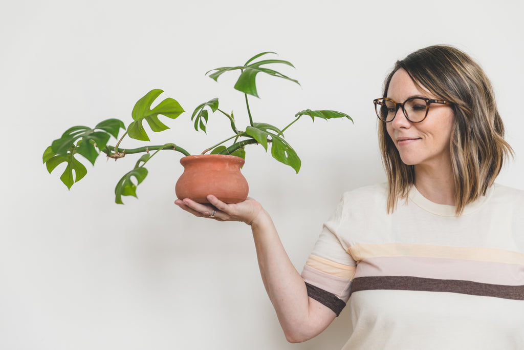Erin Harding, holding a potted plant in one hand