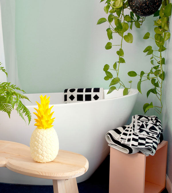a bathroom scene with bold black and white towels, a bench, and a pineapple nightlight