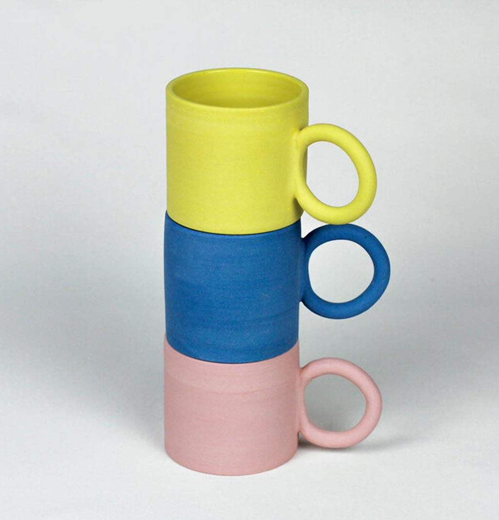 a stack of mugs in yellow, blue and pink