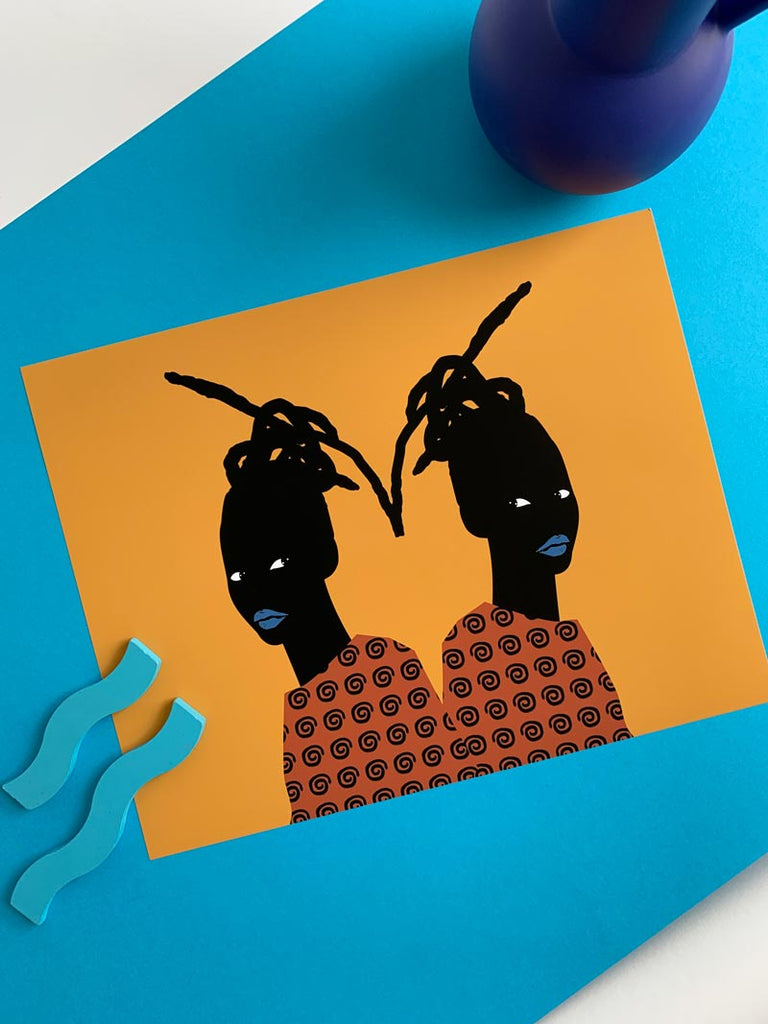 a print that depicts a black girl, symmetrically repeated, back to back. The colors are bold with gold in the background, the girl wearing an orange shirt, and her lips are bright blue