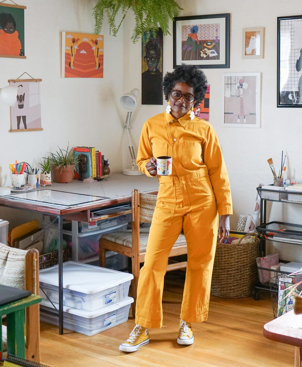 Janell Langford, standing in her art studio in a bold yellow jumpsuit