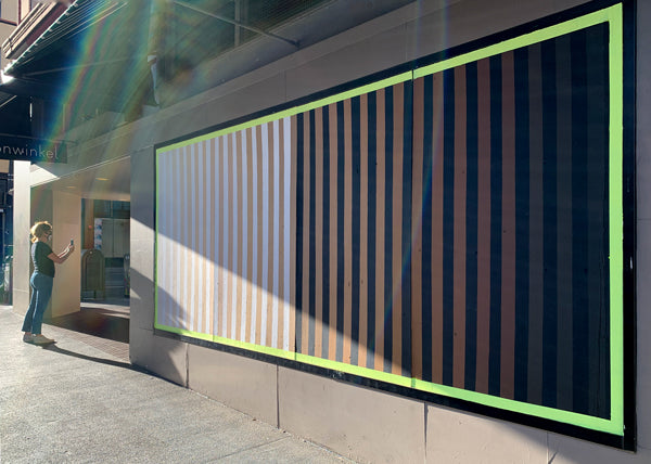 mural, with vertical stripes fading from white to black, with varying skin colors in between