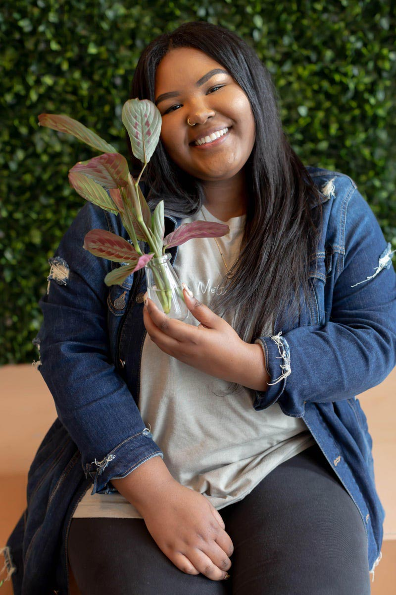 Mikayla Melson, holding a plant, and smiling