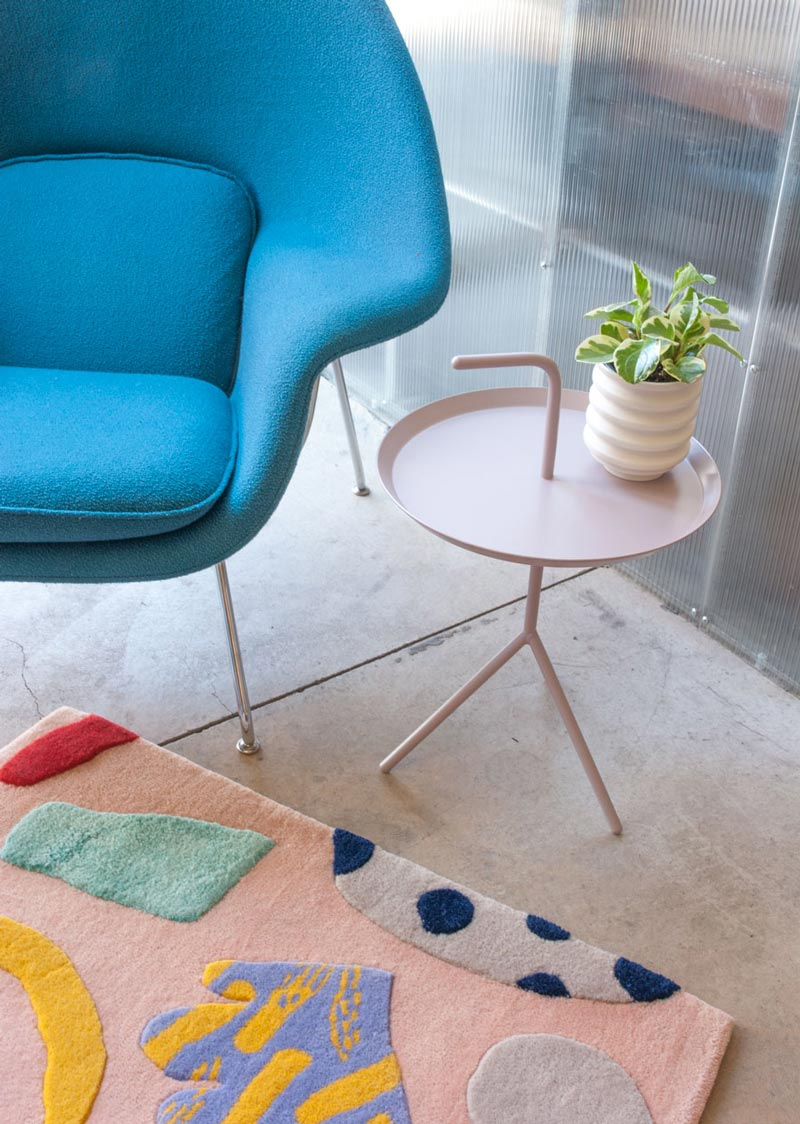 a turquoise lounge chair, a multi color rug and a lavender side table