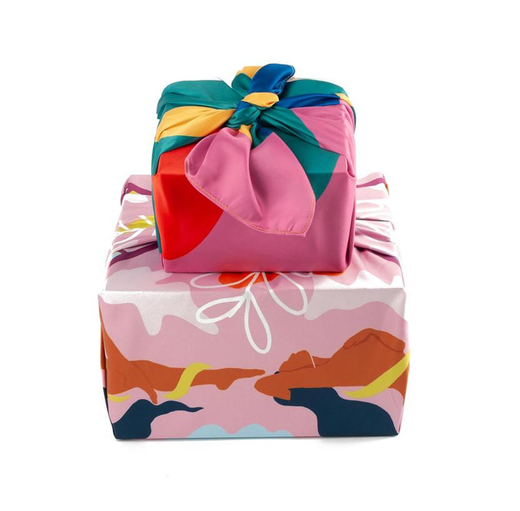 a stack of two presents, wrapped in vivid fabric in pinks and teals and browns and yellows