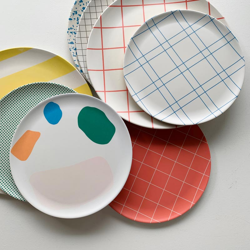 a group of plates printed with patterns of grids, stripes and dots