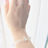 Woman's hand wearing unicorn ring and clear quartz limitless mala bracelet