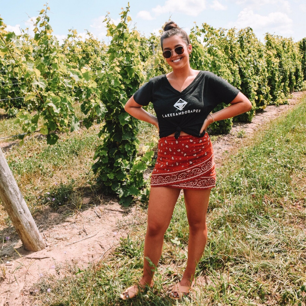 Lakes and Grapes charcoal women's v-neck short sleeve tee with white lettering accompanied by the logo. This charcoal v-neck shirt fits is perfect for Traverse City vineyards or downtown adventures.