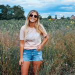 Unisex Rosé By The Bay Tee styled with jean shorts and sunglasses in Traverse City sunflower field