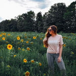 Sunflower field adventure in Traverse City wearing the Unisex Rosé By The Bay Tee in Peach