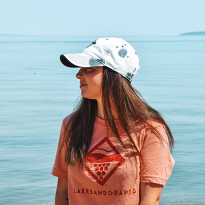 Side profile in the trendy Lakes and Grapes Greyscale Tie Die Hat along West Bay in Traverse City