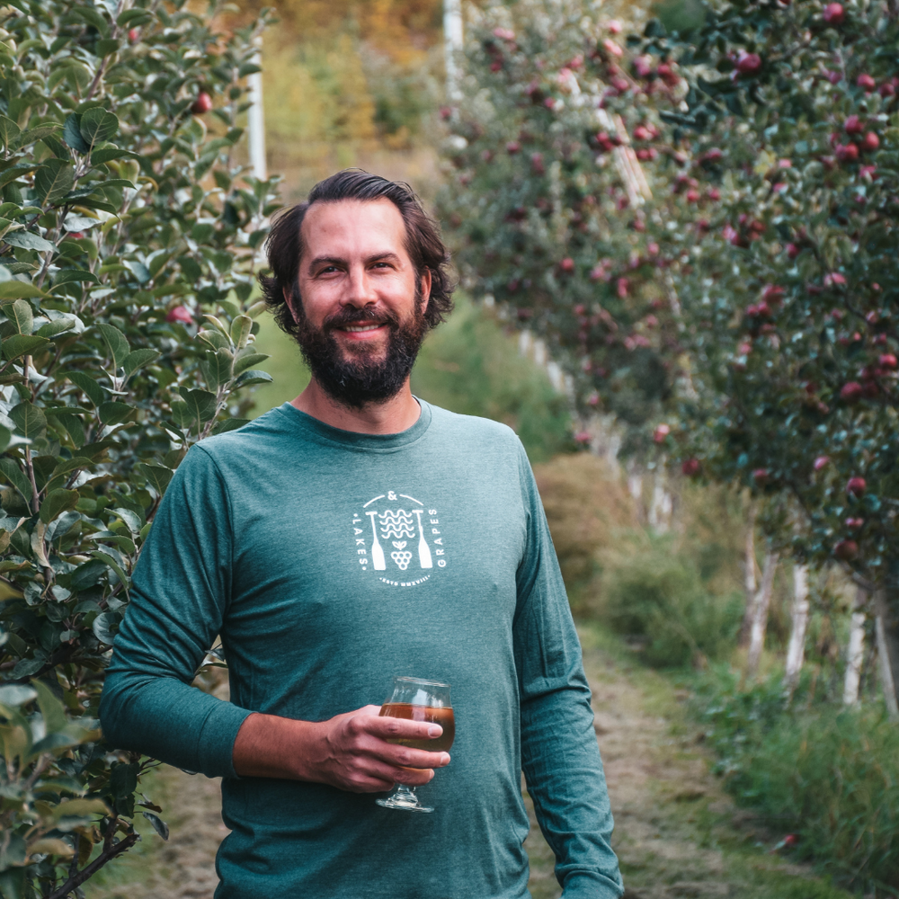 Load image into Gallery viewer, Lakes and Grapes lifestyle long sleeve tee in forest with white waves and grapes paddle logo worn on a vineyard adventure.