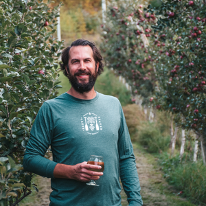 Lakes and Grapes lifestyle long sleeve tee in forest with white waves and grapes paddle logo worn on a vineyard adventure.