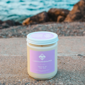 Lakes and Grapes Orchid By The Sea hand poured soy candle in glass container with metal lid.