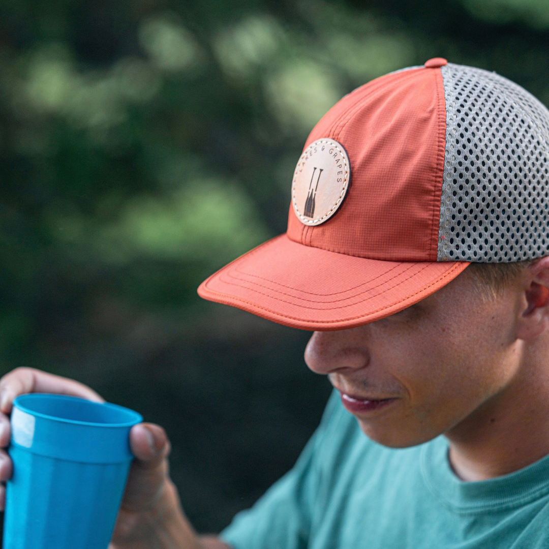 Orange quick-dry hat with mesh side and leather Lakes and Grapes paddle logo perfect for a hike or hanging by the lake.