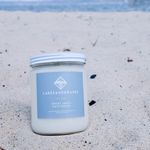 Lakes and Grapes Great Lakes Driftwood hand poured candle sitting on sand.