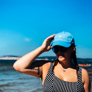Girl wearing the classic blue baseball hat and black and white striped bathing suit at the beach.