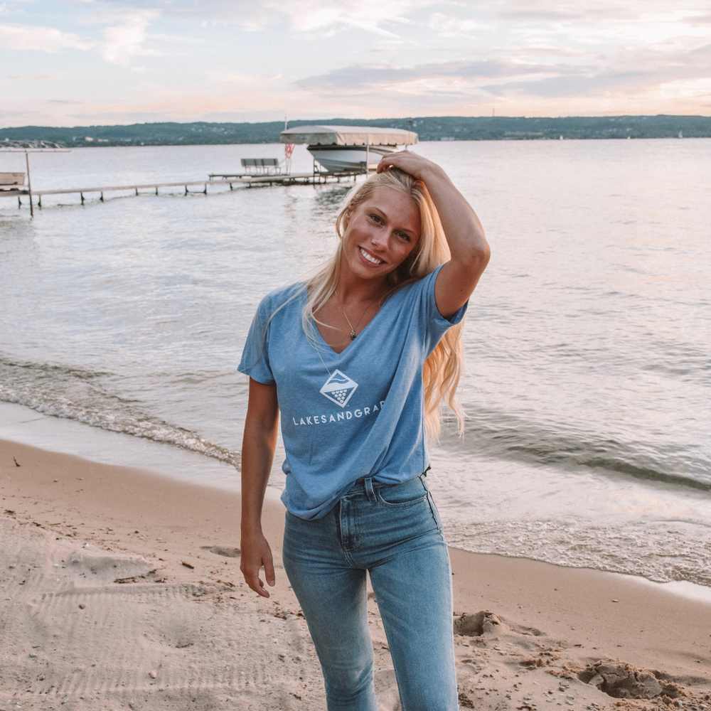 Lakes and Grapes blue unisex v-neck short sleeve tee with white lettering accompanied by the logo. This blue shirt fits in perfectly whether you're on the boat all day or around downtown Traverse City.