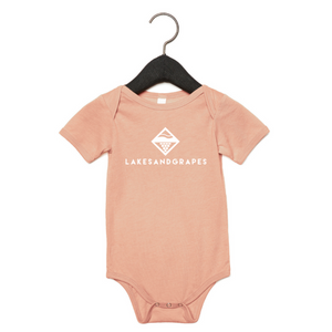 Peach baby onesie with white Lakes and Grapes logo on the front.