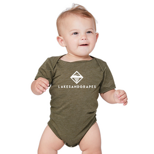 Baby wearing Olive onesie with white Lakes and Grapes logo on the front.