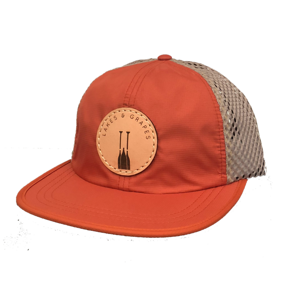 Load image into Gallery viewer, Orange quick-dry hat with mesh side and leather Lakes and Grapes paddle logo perfect for a hike or hanging by the lake.