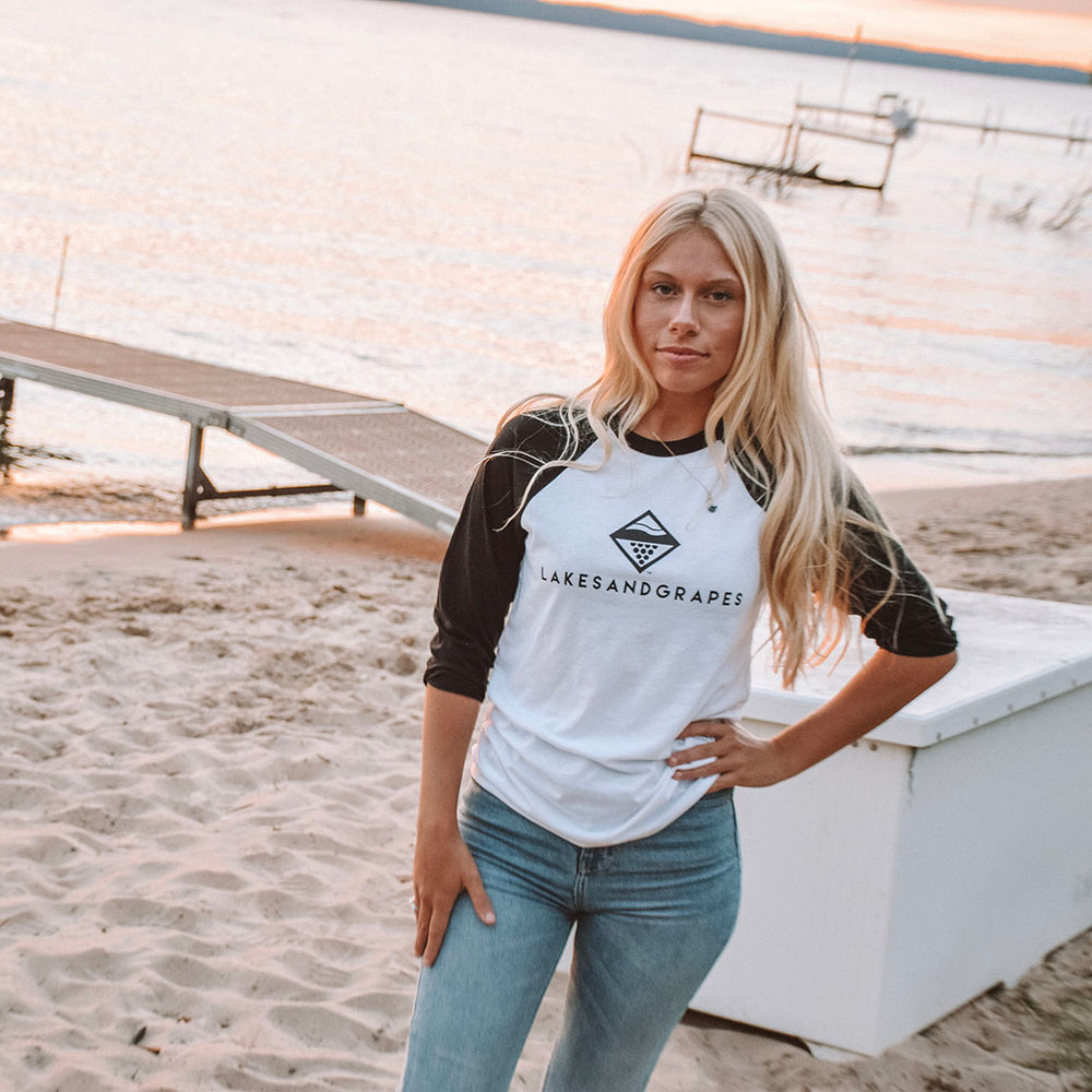Lakes and Grapes Baseball Tee with black sleeves. Traverse City apparel has the main logo and next are highlighted in black on the white space of this comfortable and casual Northern Michigan style shirt.