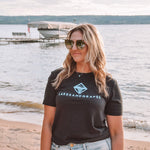 Lakes and Grapes black short sleeve tee with electric blue lettering accompanied by the logo. This black shirt is neutral so it fits in perfectly whether you're on the boat all day or around  downtown Traverse City.