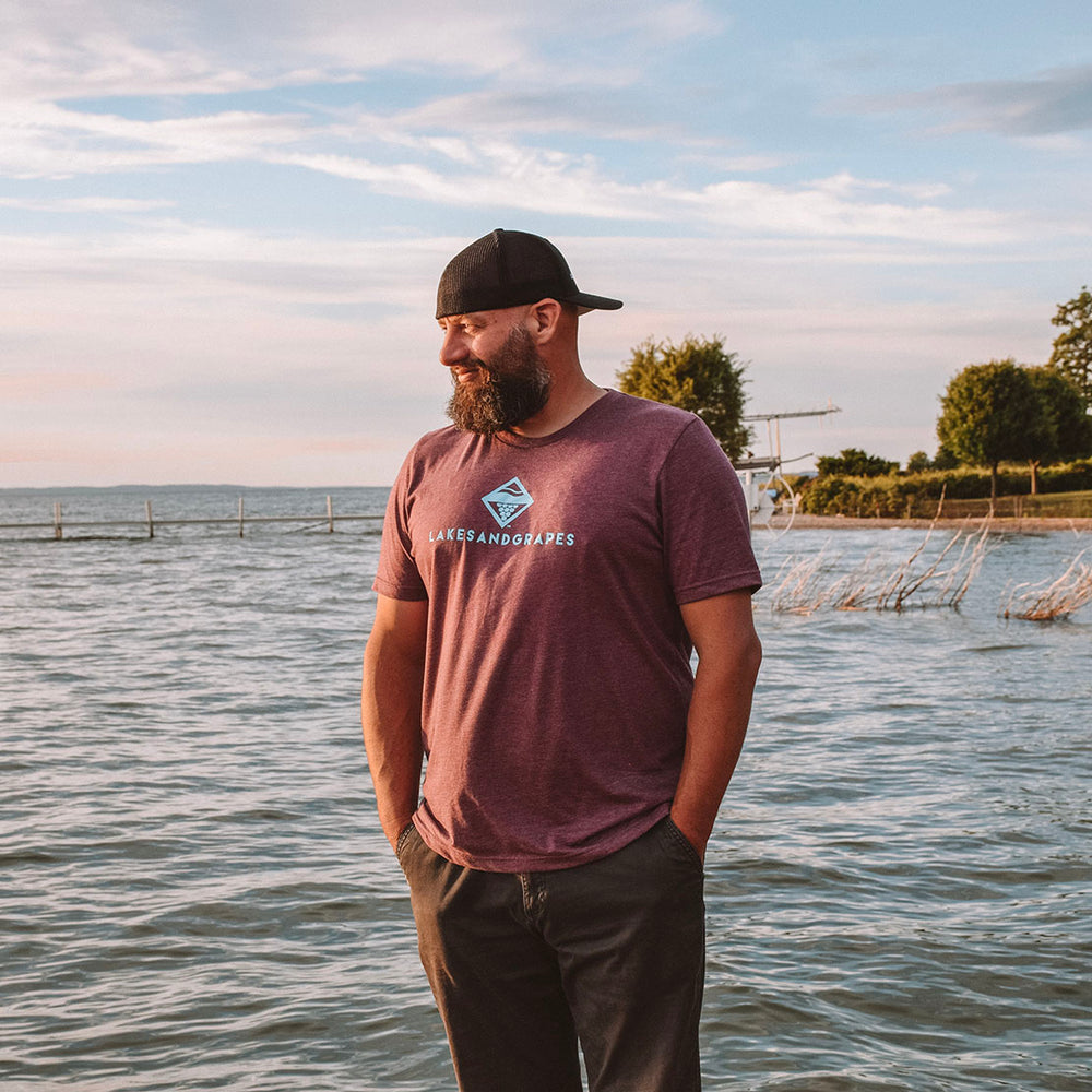 Lakes and Grapes mauve short sleeve tee with electric blue lettering accompanied by the logo. This mauve shirt fits in perfectly whether you're on the boat all day or around downtown Traverse City.