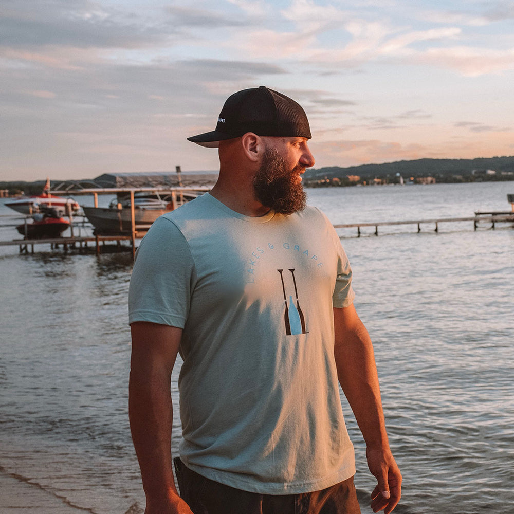 Lakes and Grapes grey short sleeve tee with electric blue and black lettering accompanied by the paddle logo. This grey shirt is neutral so it fits in perfectly whether you're on the boat all day or around downtown Traverse City.
