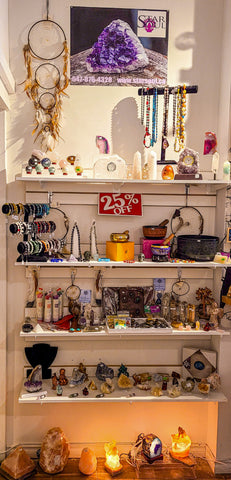 Display of crystals, jewelry and home decor items on white shelves