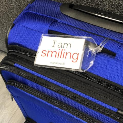 'I am optimistic'™/'I am smiling'™ luggage tag
