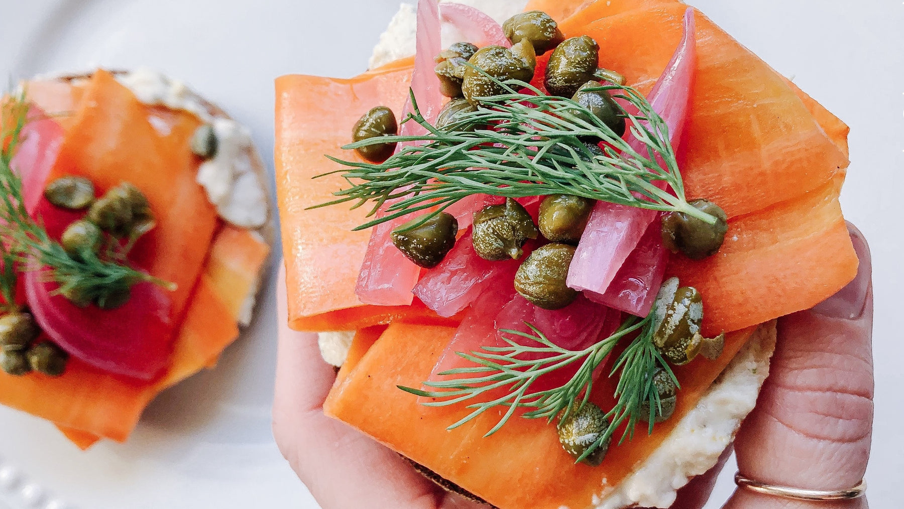 Hand holding Faux Lox Bagel with birghtly coloured smoked carrot, capers, pickled red onion, and fresh dill