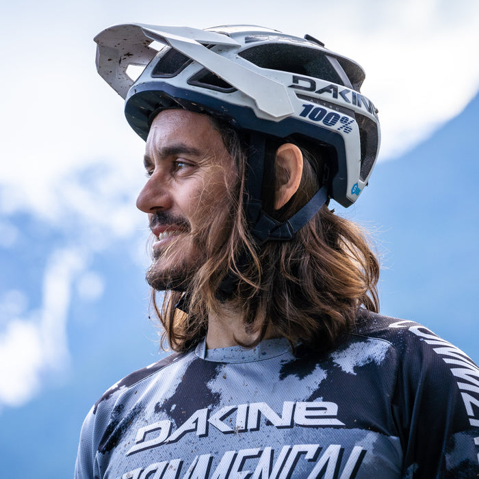 Yoann Barelli, professional mountain biker. Image of him in riding gear with mountains in the backdrop