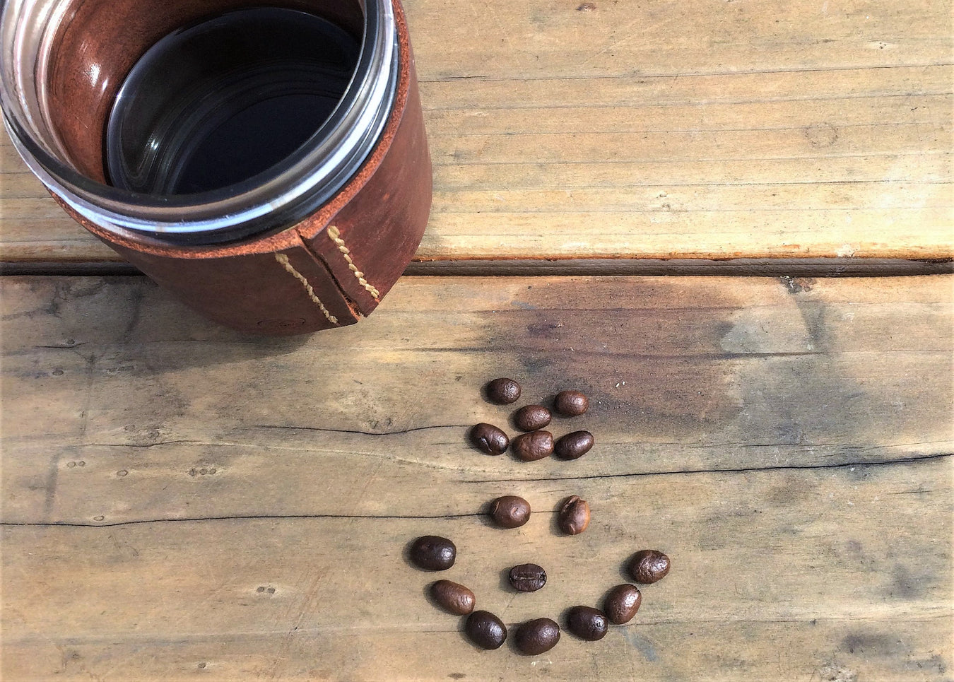 Mug of Adaptogenic Coffee on a plank backdrop with a smiley face of coffee beans