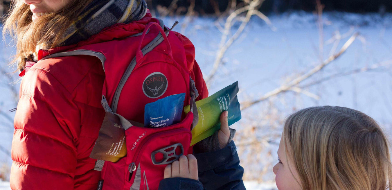 Girl tucking Mountain Bite energy bars into her mothers backpack for a hike