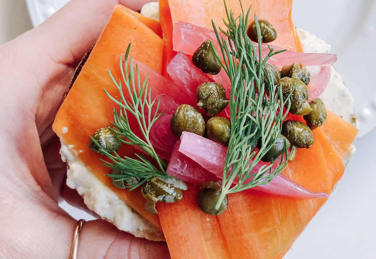 Hand holding Faux Lox Bagel on Alkeme Gluten Free Everyting Bagel with brightly coloured smoked carrot, capers, pickled red onion, and fresh dill