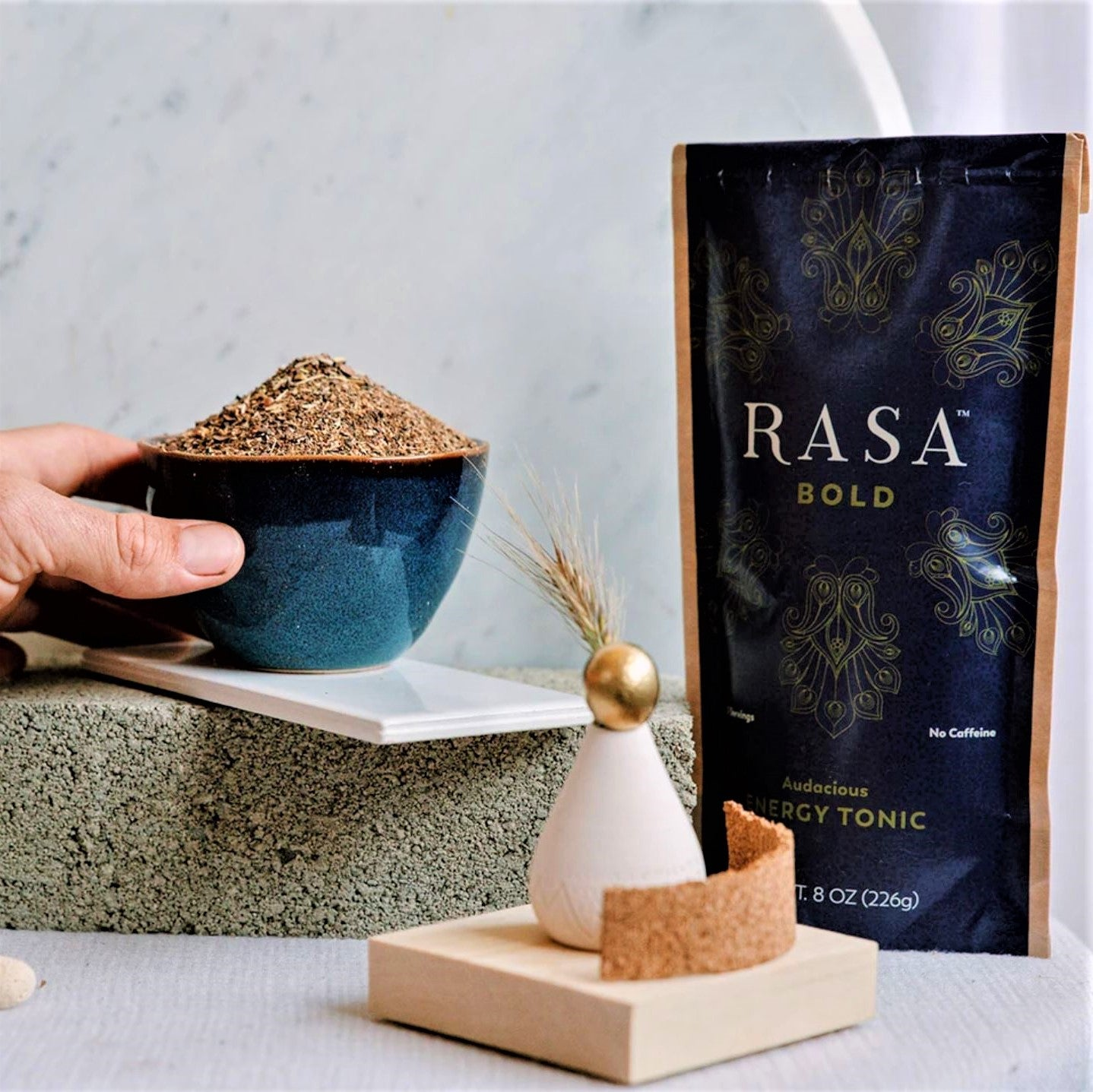 Hand holding the blended Adaptogens next to the Rasa Bold Package