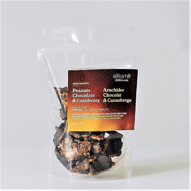 Peanuts Chocolate and Cranberry Mountain Bits granola package. Clear bag with granola filling to the top. Bright yellow, orange and brown on packaging