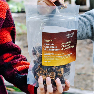Kids sharing a bag of Peanut Mountain Bits granola in the outdoors