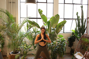 model practicing yoga in sports bra and leggings surrounded by plants