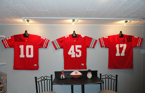 Ohio State Buckeyes football jerseys hanging on wall with JerseyGenius®