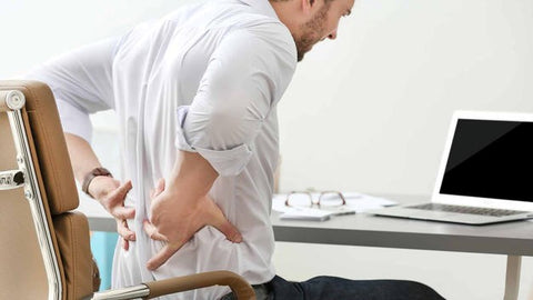 A man with back pain sitting on a chair