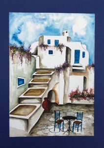 greek island watercolor painting with white houses, a table and chairs and baby blue sky