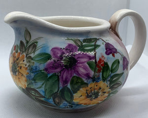 white ceramic milk jug with purple and yellow flowers and green leafs