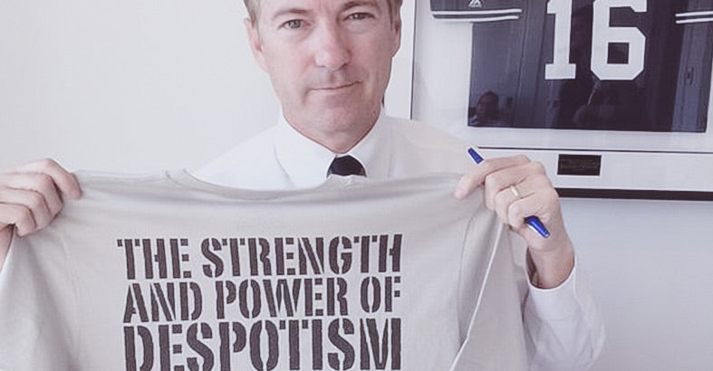 Rand Paul holds up a t-shirt from Liberty Maniacs featuring a quote by American Revolutionary Thomas Paine