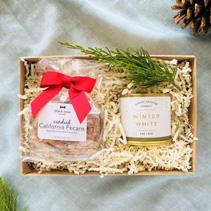 Kraft box with Candied california pecans and winter white candle with fresh holiday greenery curated for holiday gifting.