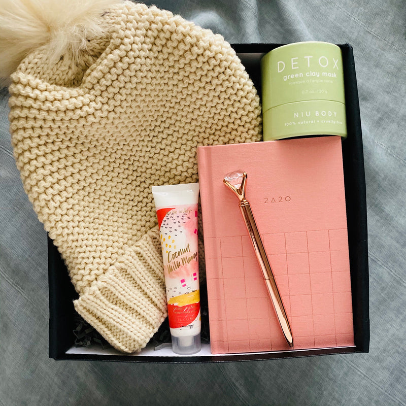 A black gift box with pom beanie,  2020 planner, rose gold pen, hand cream and detox clay mask make a perfect gift for her.