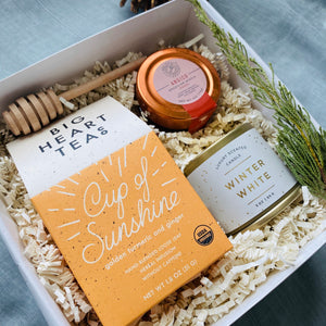 Holiday gift box with Tea, honey, candle and wood dipper in it.