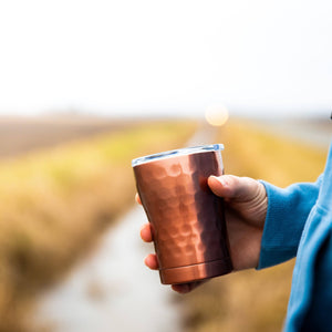 A man holding 12 oz Hammered Copper Stainless Steel Tumbler
