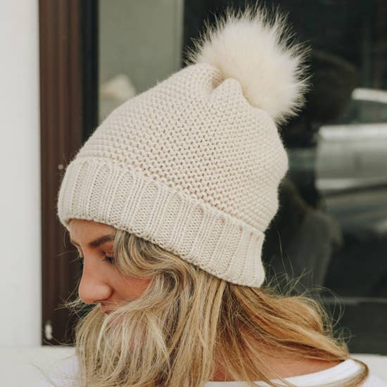 A girl wearing oatmeal color pom beanie